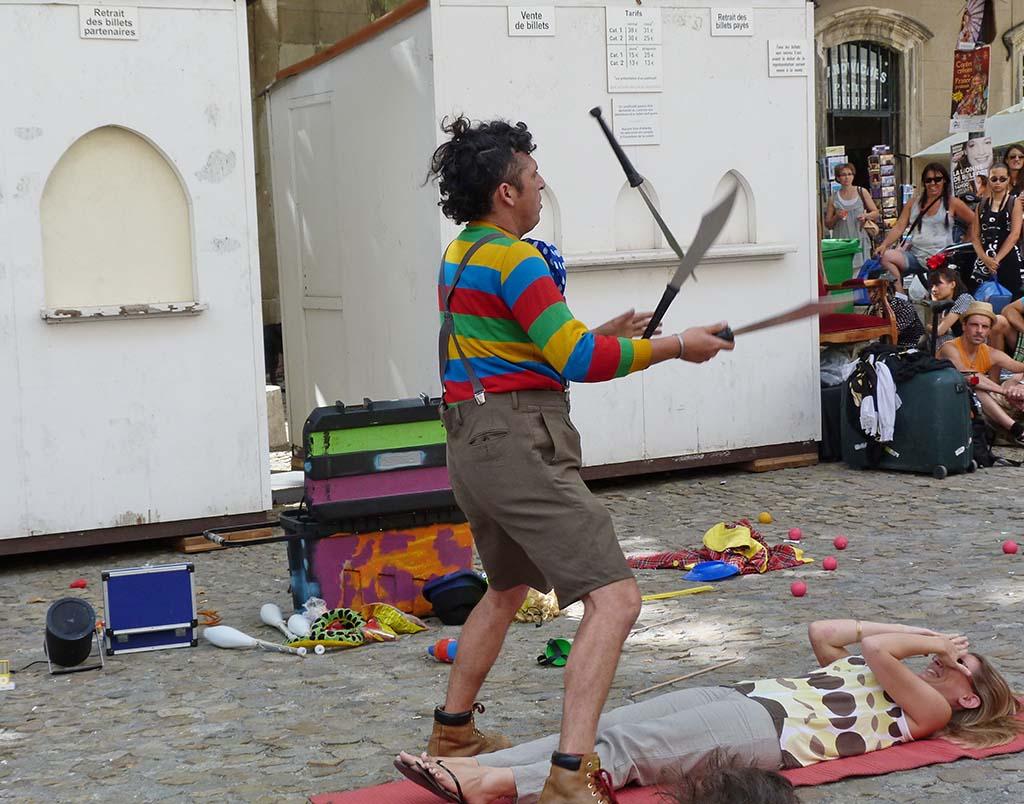 A juggler juggles large knives