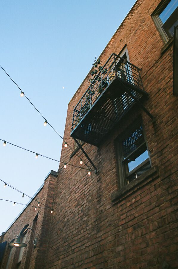 Looking up at the side of a brick building with a small balcony