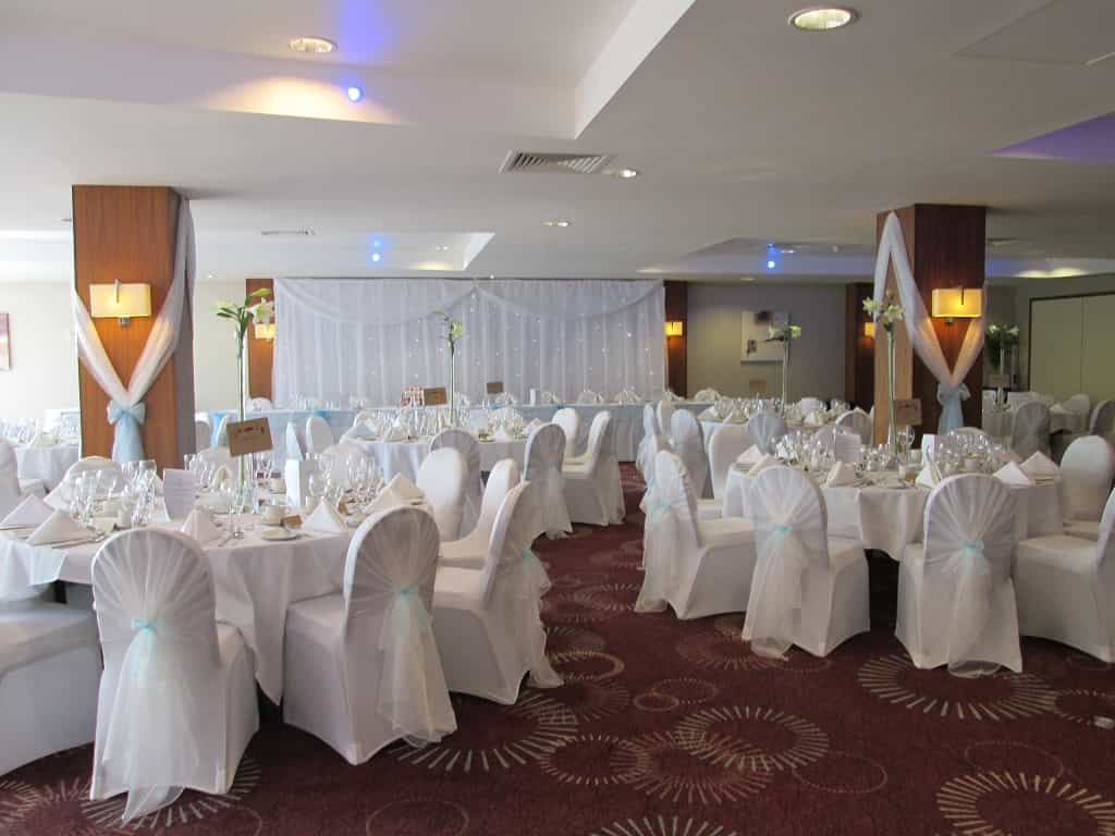Wedding breakfast venue dressing with white and ivory decor