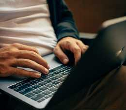 A man typing on his laptop which sits on his lap