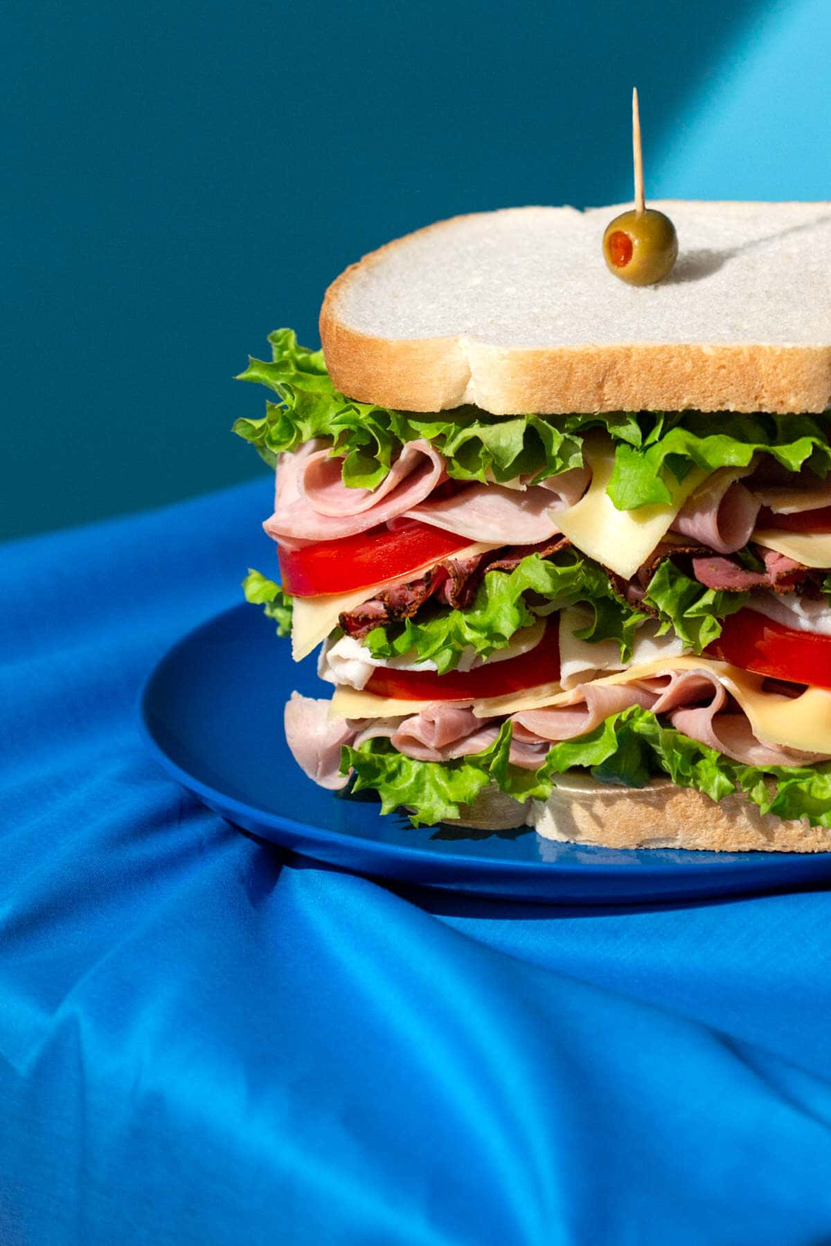 ham and pastrami cheese sandwich shot in a pop art style with blue props