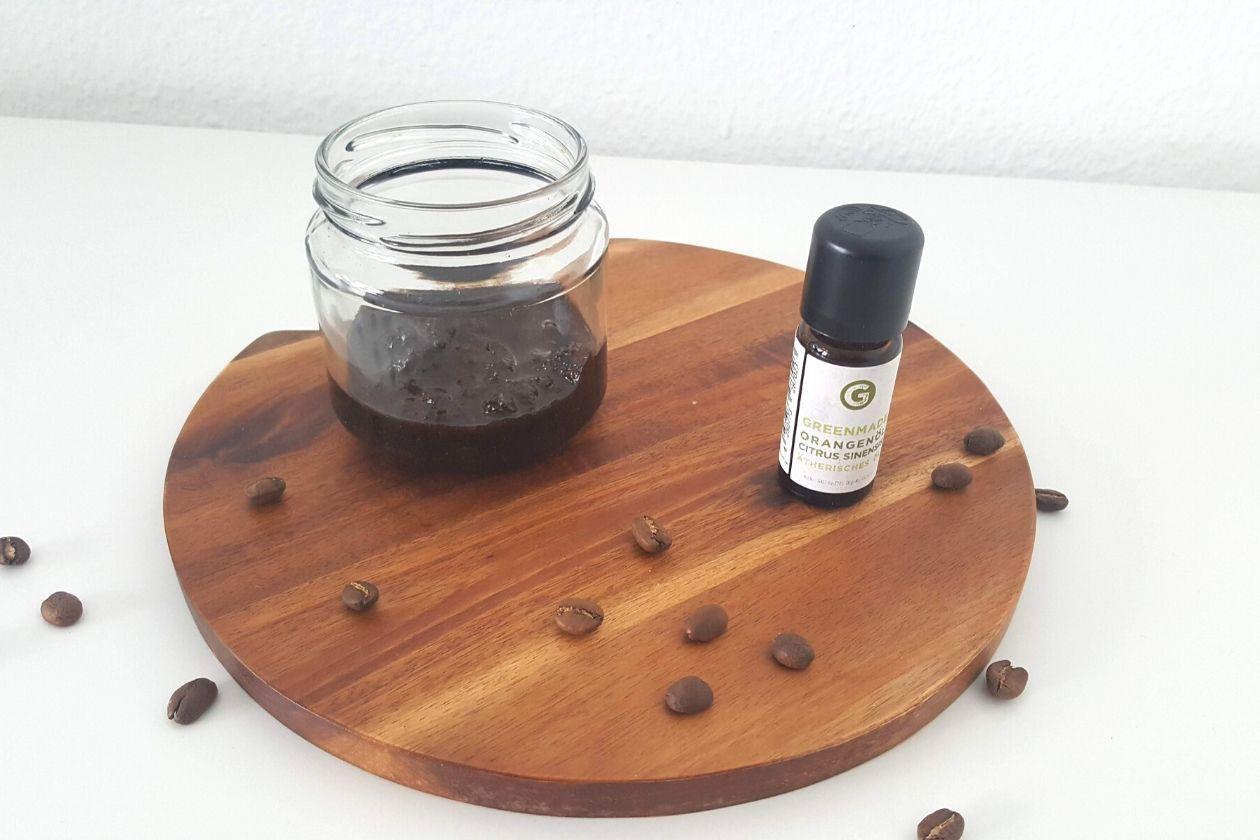 Das Zero Waste Kaffee-Orangen Peeling in einem Schraubglas und das Orangenöl daneben, beides plaziert auf einem Brett. Kaffebohnen liegen drum herum.