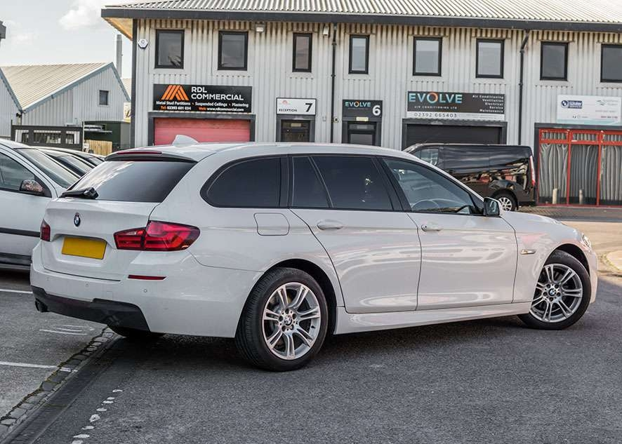 White BMW 5 series with tinted windows from rear