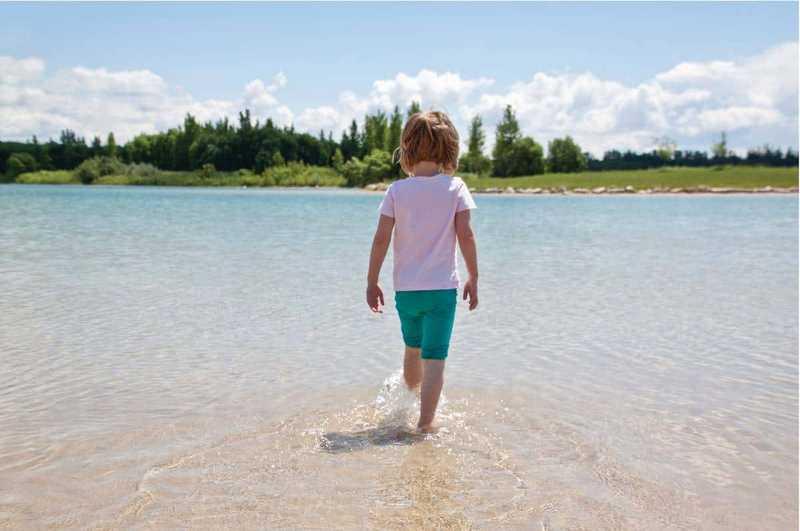 Child kicking water in Saskatchewan lake