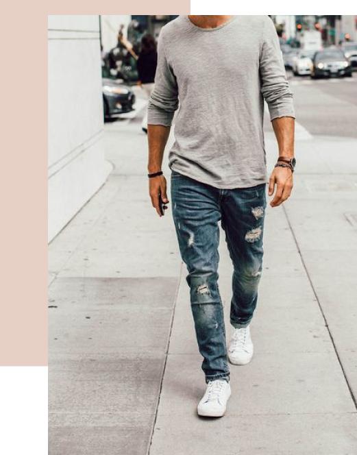 Un homme portant un jean dechiré dans la rue
