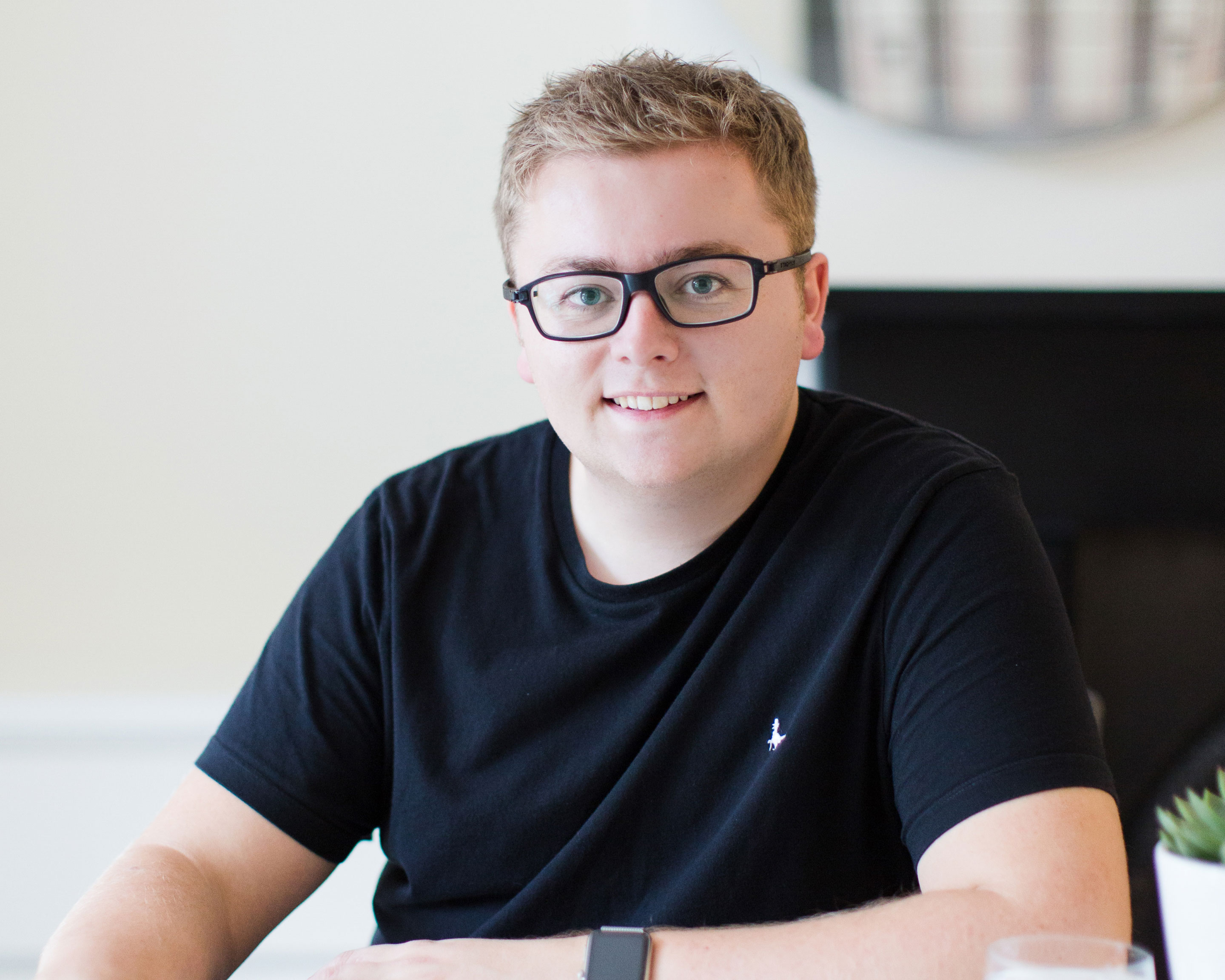 Jack Watkins in black glasses and black t-shirt smiling at the camera
