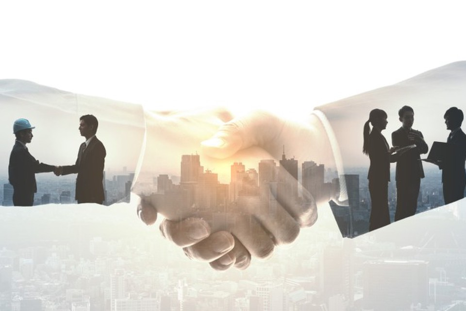 Policymakers and community members collaborate within an image of clasped hands superimposed over a cityscape to illustrate the concept of social work policy advocacy.