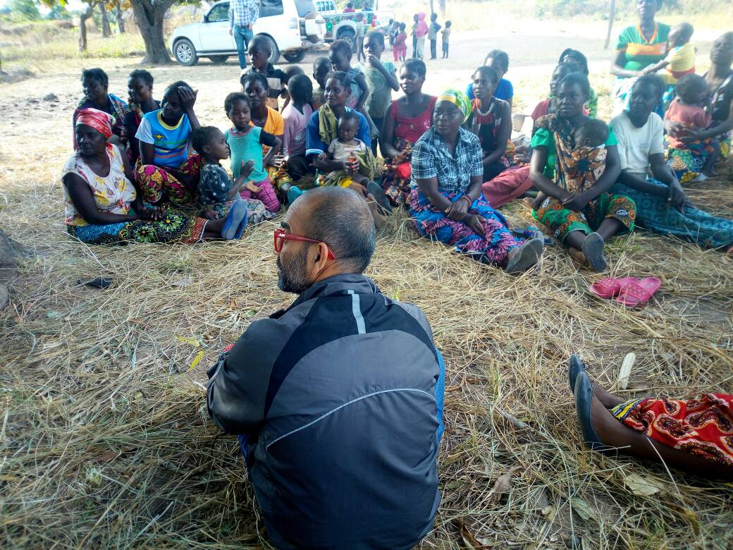 BanQu co-founder, Ashish Gadnis, sits with Zambian farmers, teaching them about the BanQu app