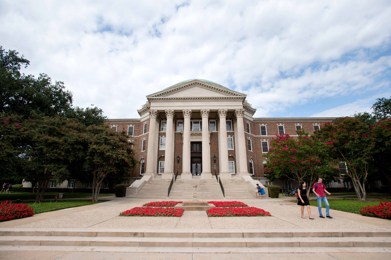 Students walking the stairs to Dallas Hall at Southern Methodist University on a cloudy day