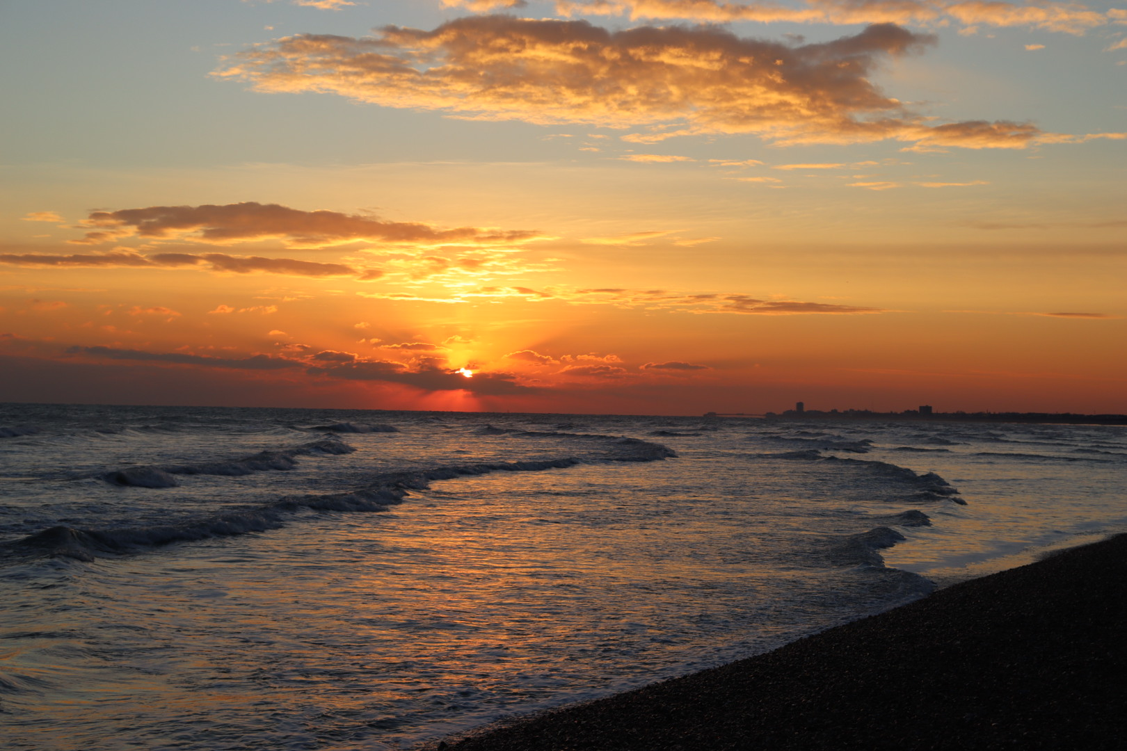 Rippling waves beneath an orange sky as the sun sets.