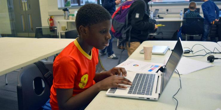 A boy coding on a laptop