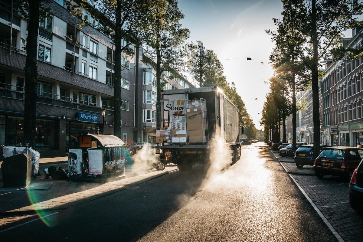 A delivery truck with its cargo door open drives down a street in a European city.