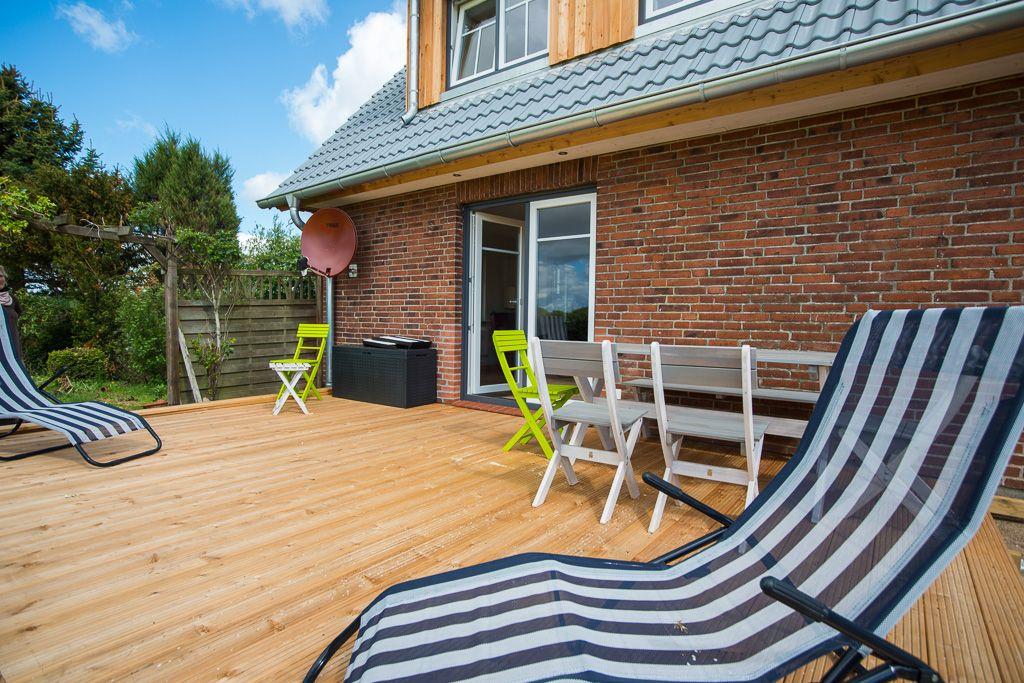Holzterrasse mit Liegestühlen und weißen Holz-Gartenmöbeln