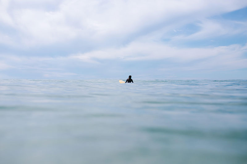 Photo from the water with a surfer on the horizon