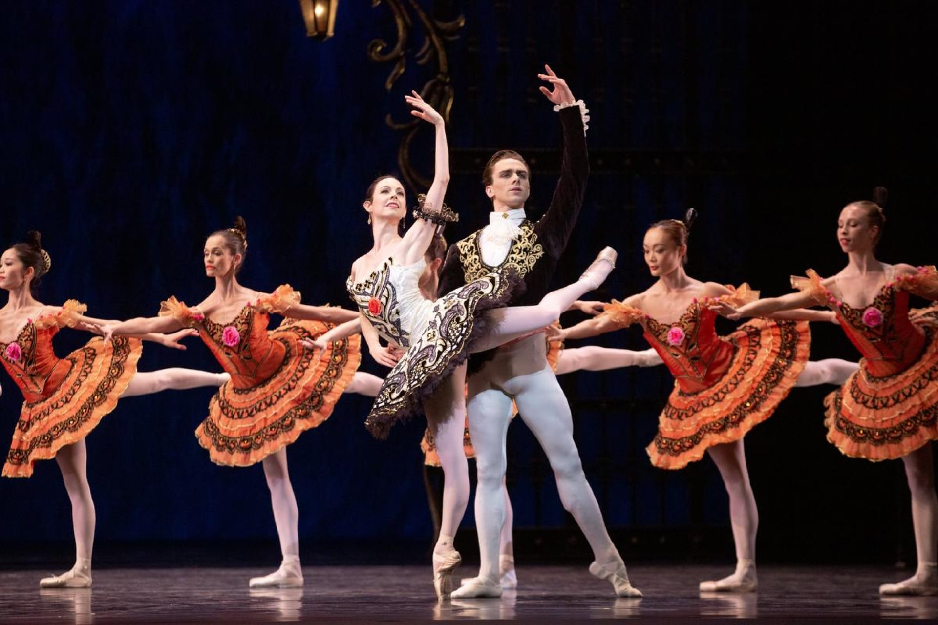 Couple black and white outfits hold pose in front of chorus of ballerinas in bright orange tutus.