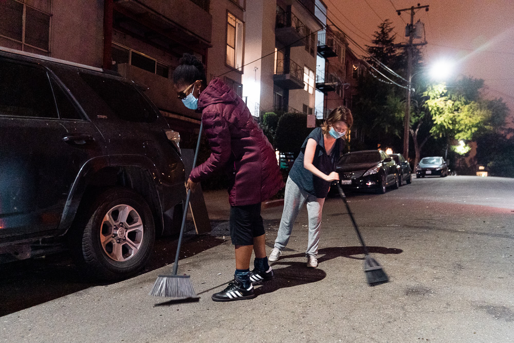 Neighbors of Adams Point sweep their street of glass and other debris left by protesters as they were dispersed by police during the 'Justice for Jacob' protest in Oakland, Calif., August 26, 2020.