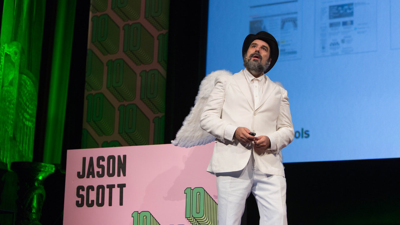 An enigmatic conference speaker, wearing a white suit, top hat and angel wings
