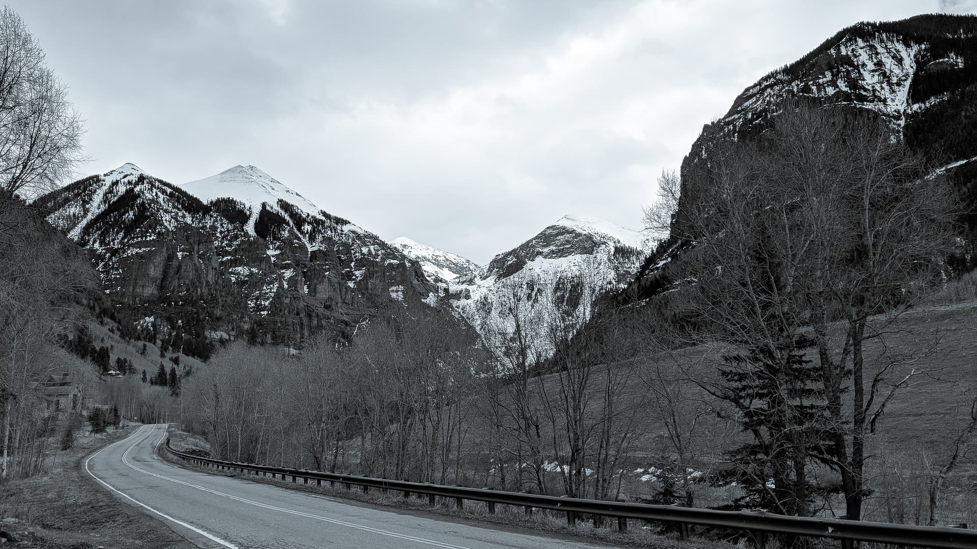A black-and-white photo of a mountain road winding along a valley next to a tree-lined creek. Beyond the trees, three distinctly triangular snow-capped peaks can be seen.