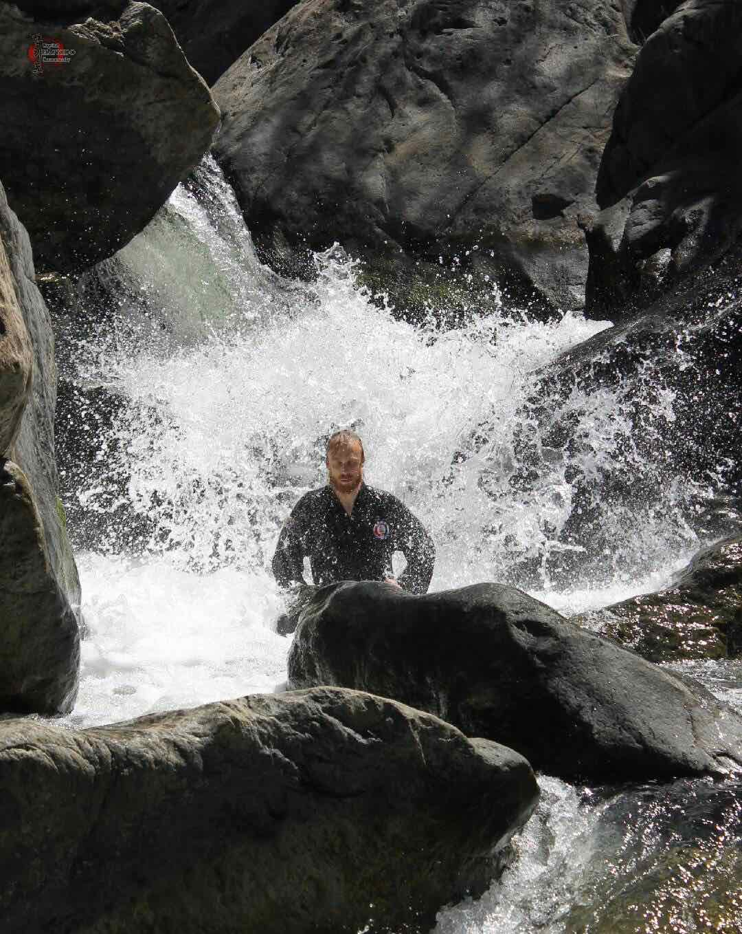 Serious Michael mediates under a waterfall.