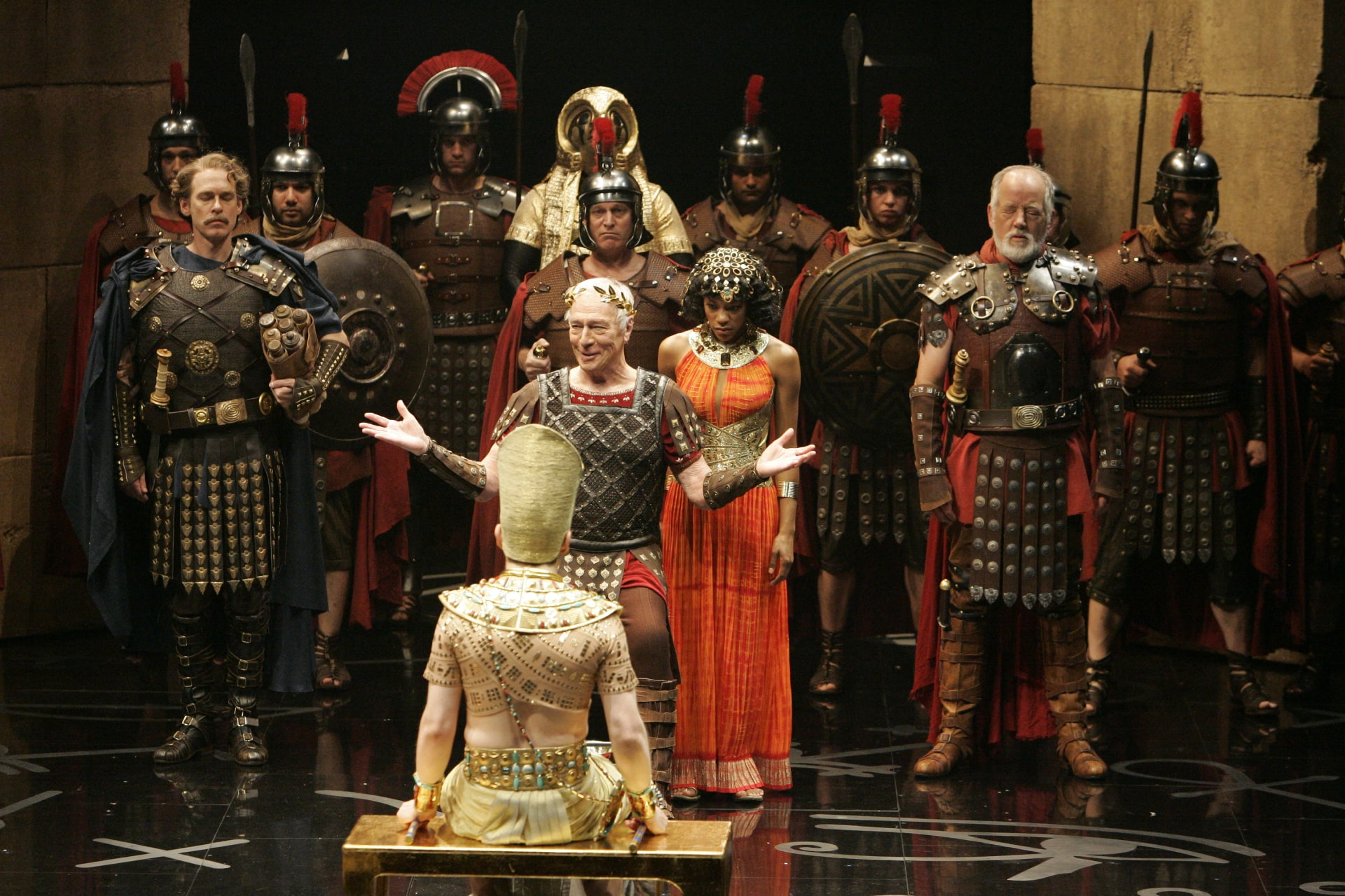 Roman leader lectures Egyptian boy, flanked by Egyptian queen in orange and company of Roman soldiers.