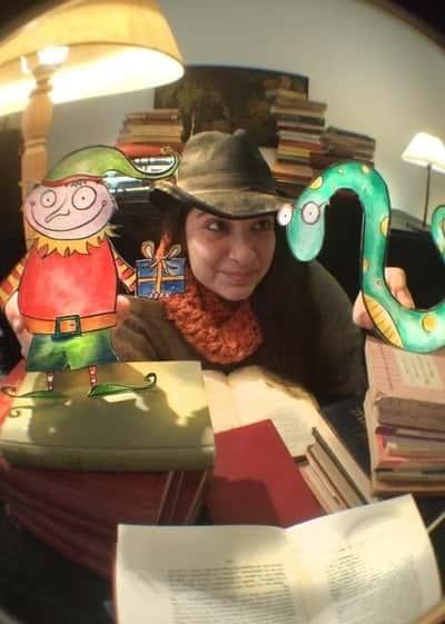 Η Αγγελική φοράει καπέλο και διαβάζει βιβλίο μαζί με ζωγραφισμένους χαρακτήρες.