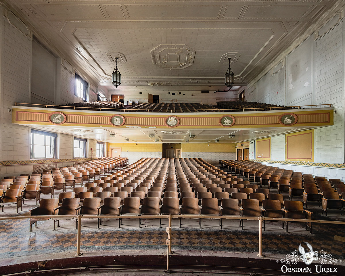 abandoned auditorium with stage and rows of seats