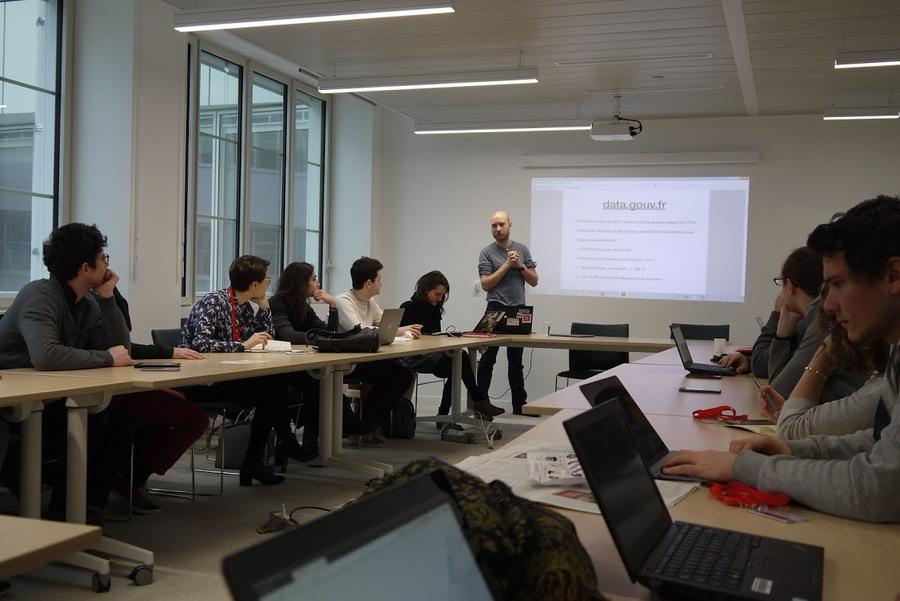 """Un homme présente dans une salle de réunion organisée en U, devant une présentation où l'on peut lire """"data.gouv.fr"""""""