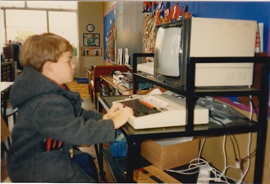 Young Rob Kendal sitting at a BBC computer