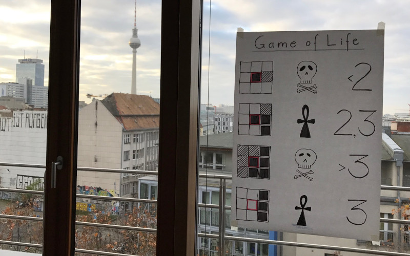 a poster of the rules of game of life, put up on a window in Berlin