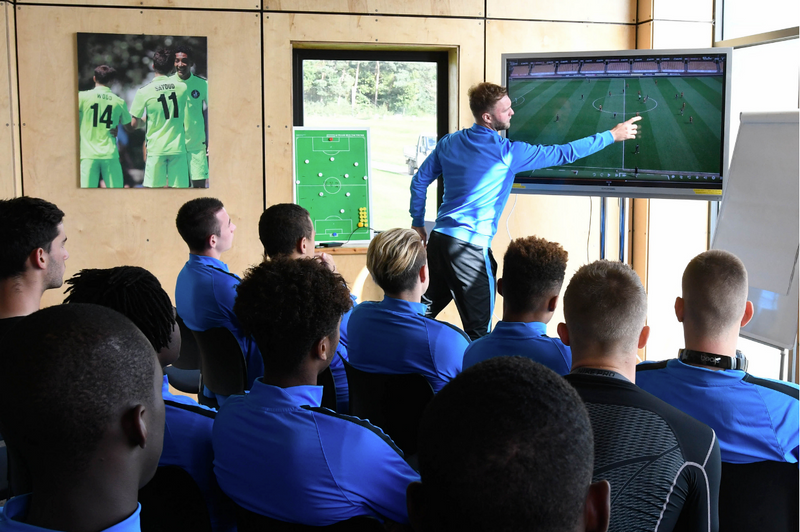 Coach discusses football match tactics with team