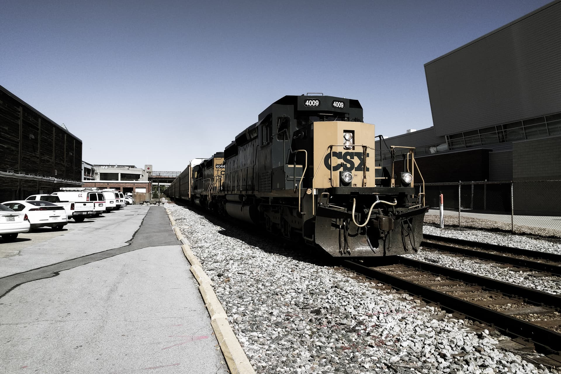 A black and yellow train approaches the camera obliquely. The train is so long that it stretches as down the tracks as far as can be seen.