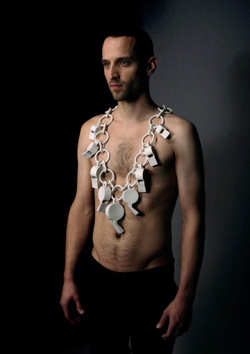 A man wears a long white porcelain necklace of eight oversize whistles, linked together by a chain.