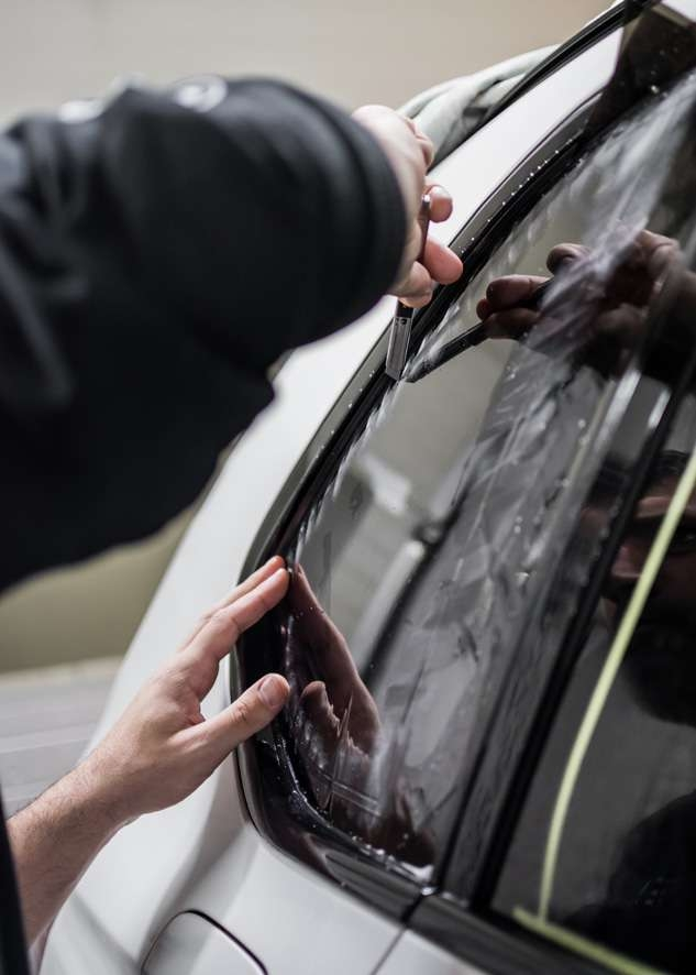 Window tinting film being cut for White BMW X5