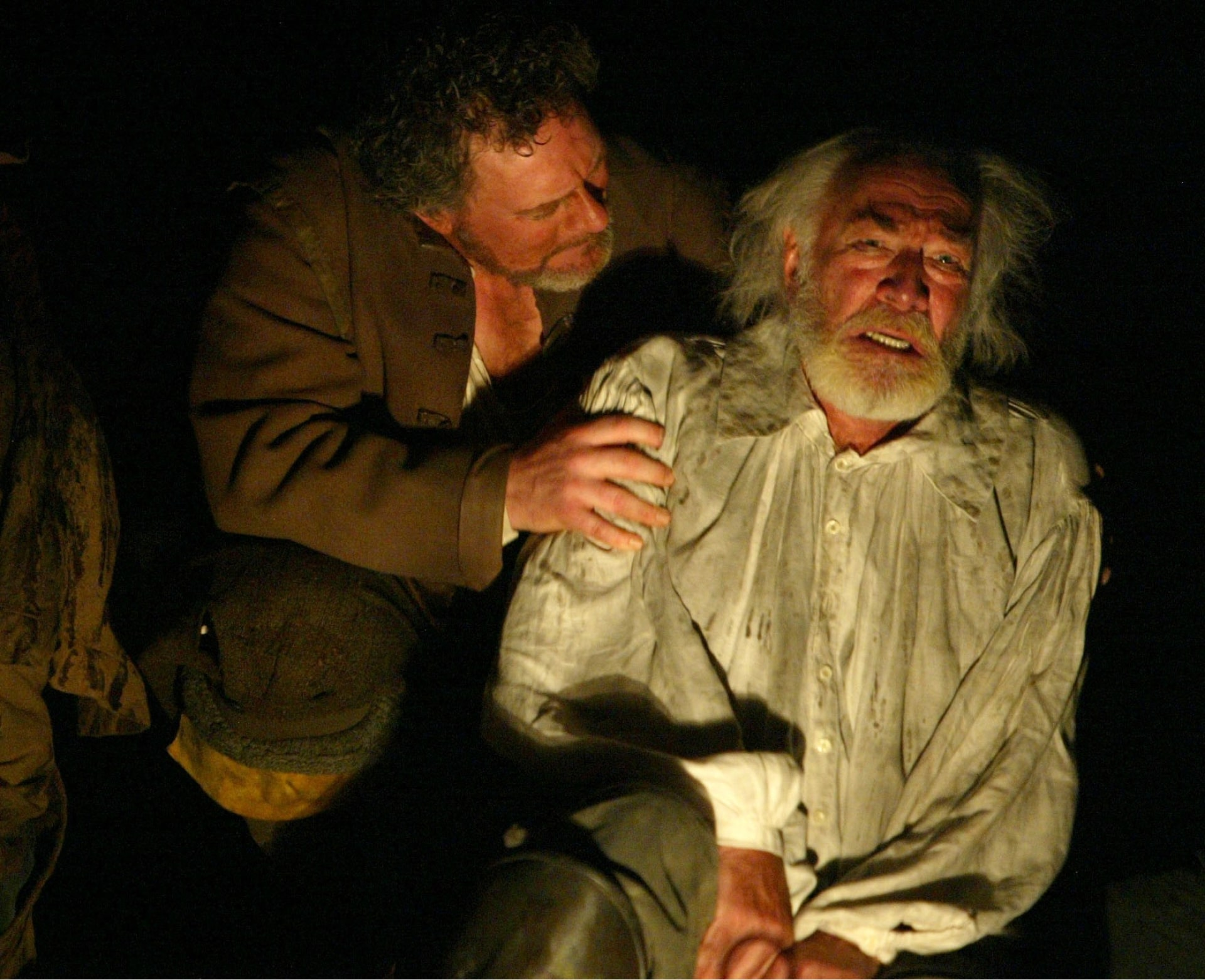 Bearded old king is consoled by scruffy man lit by lantern.