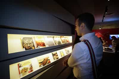 Brightly lit shelves with cookbooks are on display, with a visitor looking at them.