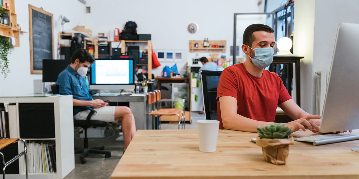 UX designers social distancing in an office, and wearing masks