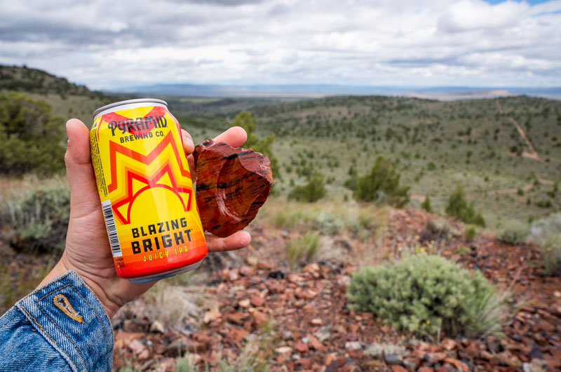Someone holding a can of Blazing Bright and piece of Black Obsidian with Glass Butte in the background
