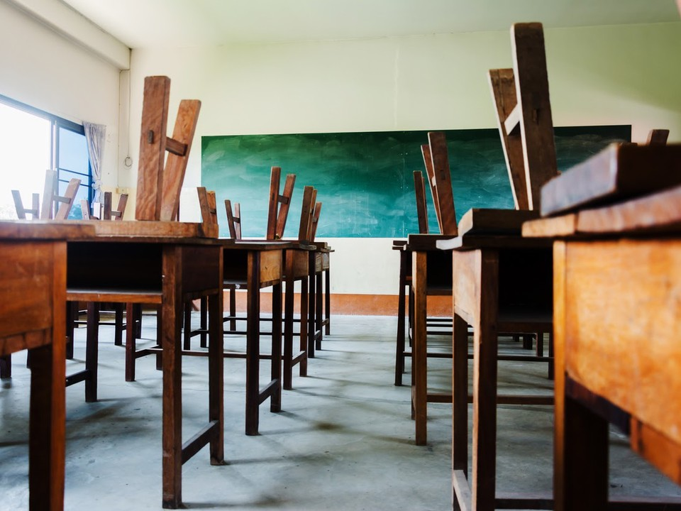 An empty classroom with old wooden desks, chairs placed upside down on desktops, and an old-fashioned chalkboard.