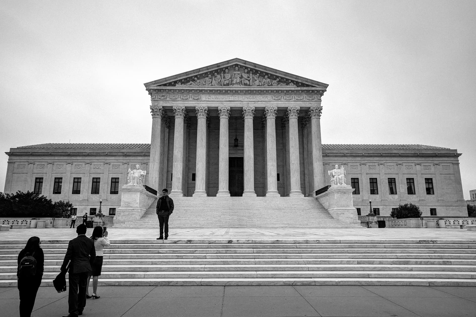 A black-and-white photograph of the entrance to the United States Supreme Court. On the steps to the left, a man is having is picture taken by a woman, while two other people look on.