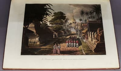 A book showcasing a coloured illustration of a street. British soldiers are marching through. In the distant background, there is the Golden Pagoda.
