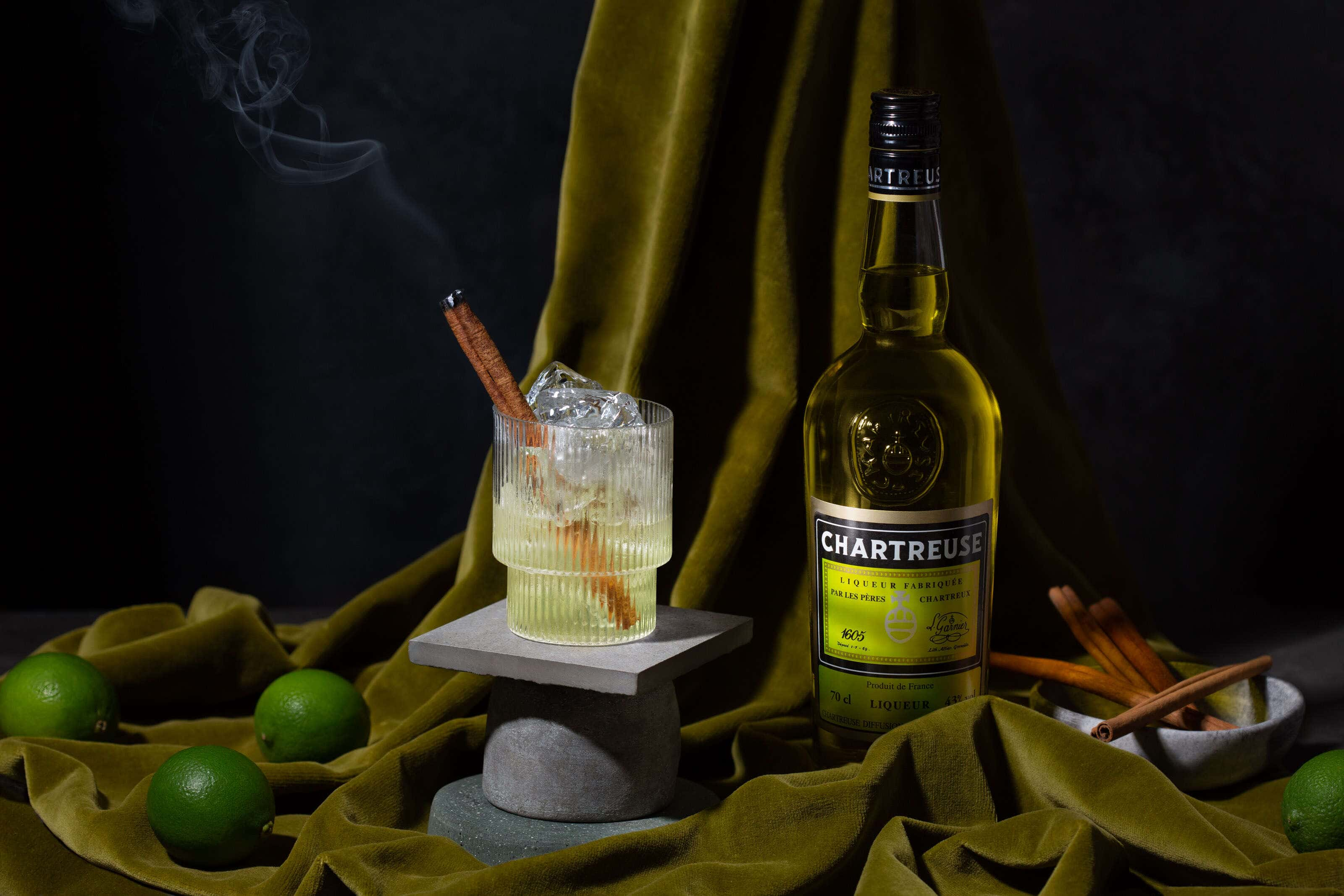 charteuse_bottle_and_cocktail with cinnamon stick smoking and limes on the table
