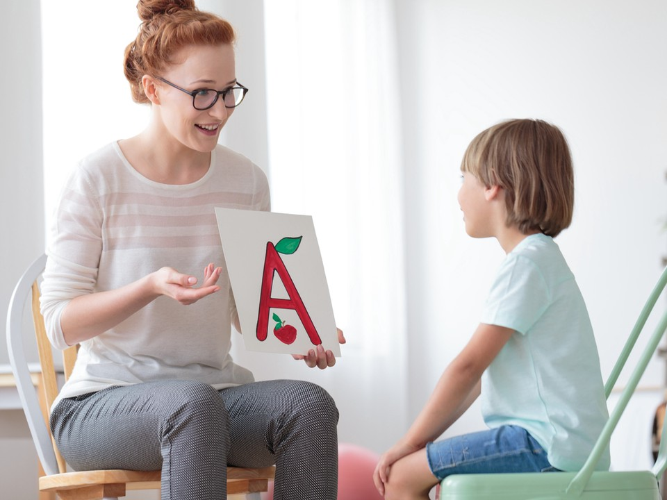A female teacher holds up a card with an A in front of a young student