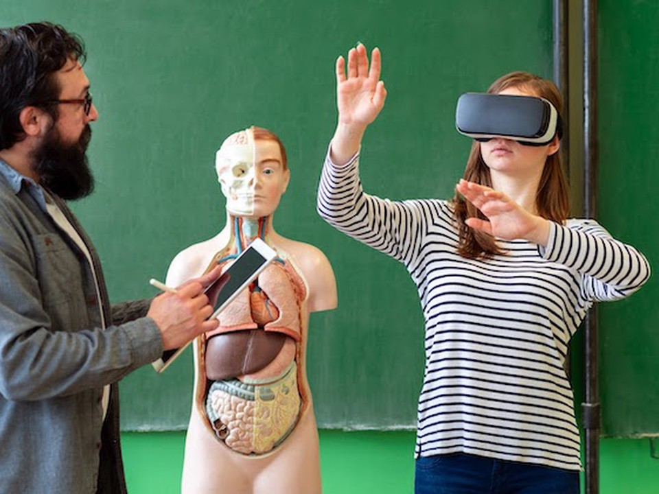 A male biology teacher instructs a female middle school student using virtual reality technology.