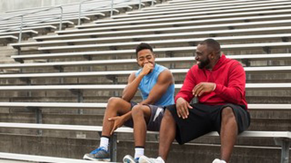 Two man with atletic clothes seated on the bleachers