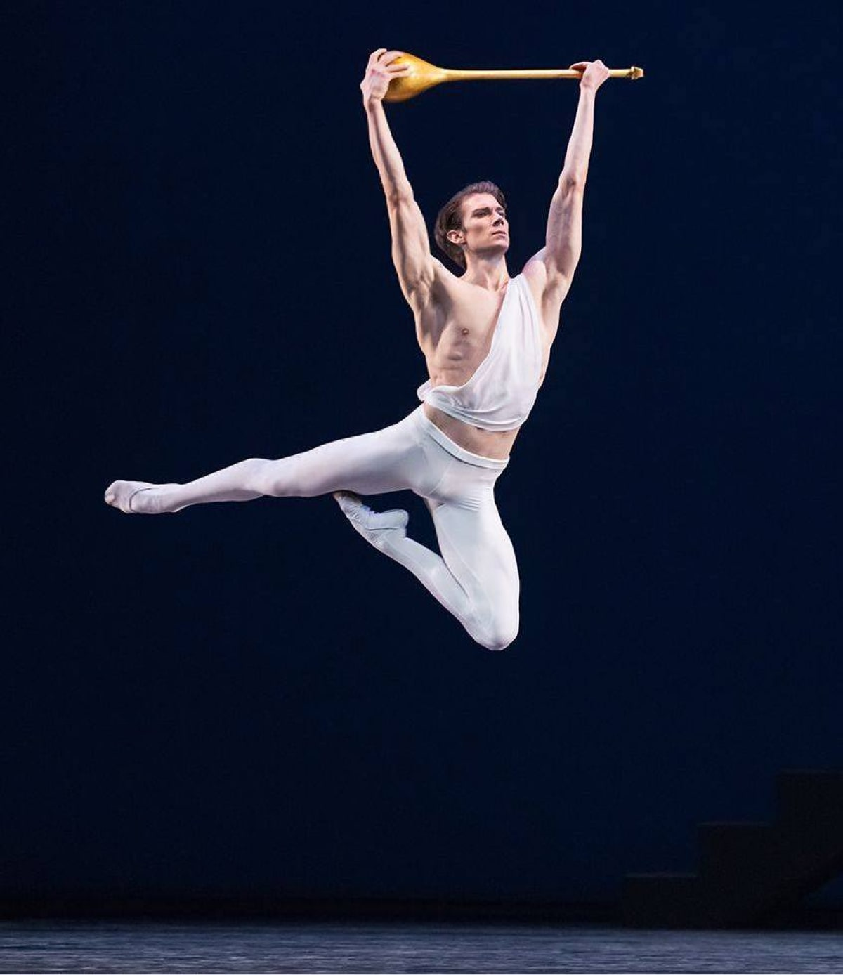 Bare-armed dancer in white tights leaps with golden lute held aloft against dark blue background.