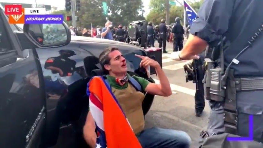 Edward Badalian crying with a broken nose while leaning on a cop car.