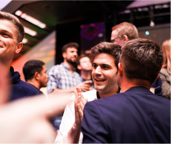 Group of smartly dressed men standing together at some kind of party event.