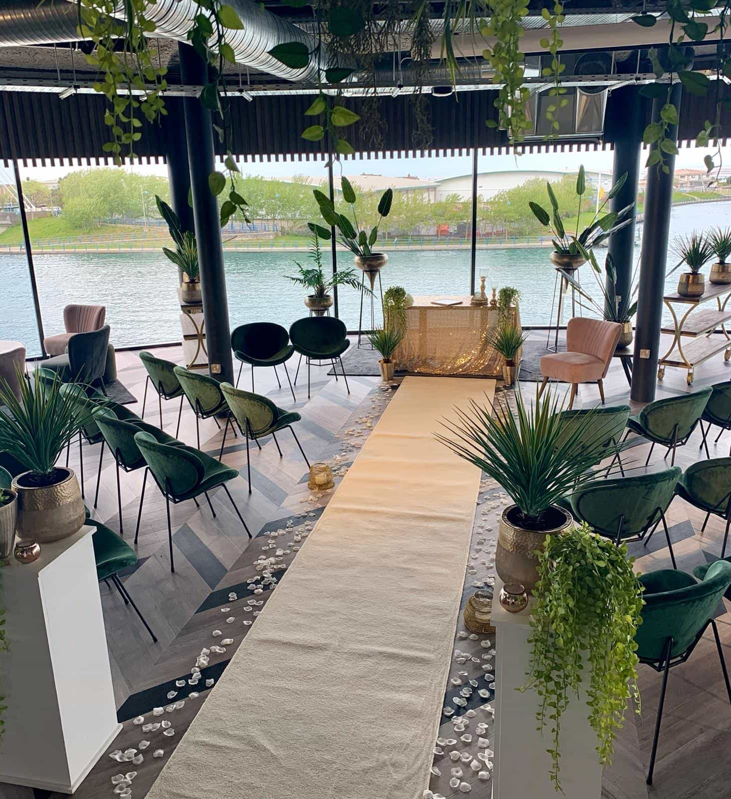 Wedding ceremony with rustic green decor and white aisle runner at Bliss hotel, Southport