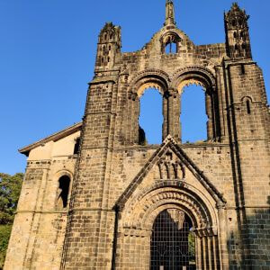 Looking up at Kirkstall Abbey against a blue sky in the afternoon