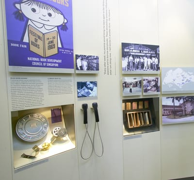 A photo close-up of a wall display, featuring the 1960s history of the National Library. On the top left, there is a poster with a cartoon girl and her book, by the National Book Development Council of Singapore. In the center, there is a small TV screen with audio handsets. On the right showcase, there is a wooden box with old due date cards on display.